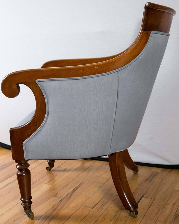 A pair of 19th century mahogany bergère or library chairs, with a nice sloped back rail with scroll arms, upholstered seat and back on turned legs at the front and swept back legs at the rear, standing on brass castors.
