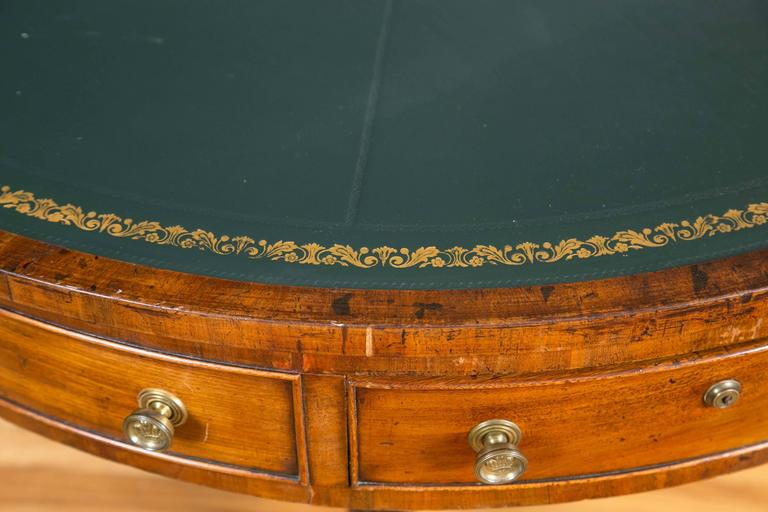 The circular top with gilt-tooled, green leather surface above four pull-out frieze drawers and four simulated drawers. The top sits on a turned pedestal base with three reeded and splayed legs that terminate in brass caps and castors.