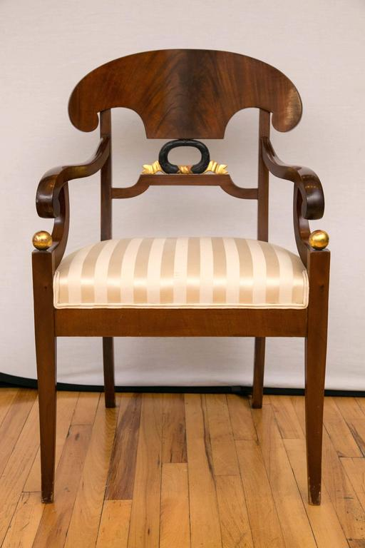 An exquisite pair of armchairs. This pair of Biedermeier armchairs feature fountain form back, scrolled arms joining the from legs topped with a gilt ball motif. The armchairs are raised on four saber legs. Wonderful rich color.