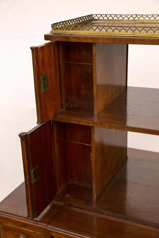 A lovely Regency ladies' writing desk with a pull-out adjustable easel writing surface. The high stacked center is comprised of four compartments filled with locks, and fitted with a heart design brass top rail. Side drawers open for more storage