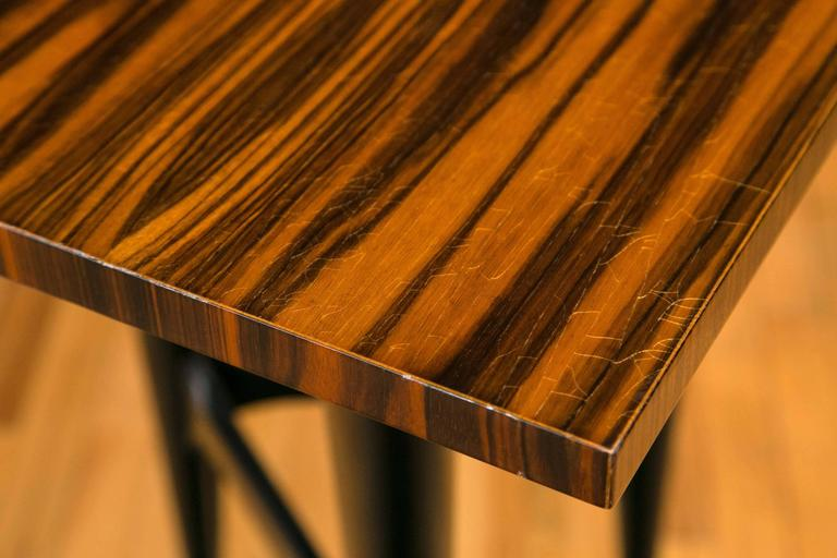 Panels of Macassar ebony cover the desk top which sits on tapering tripod blackwood legs. The face of the desk conceals three drawers, the center drawer containing compartments.