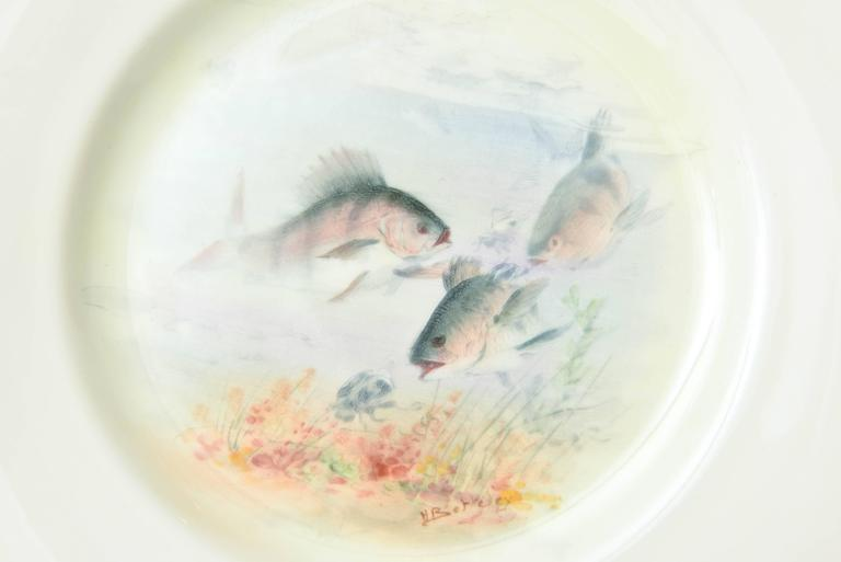 A Classic and elegant fish service consisting of 12 artistically painted fish in their full flora and fauna ground. Trimmed in 24-karat gold and perfect for display, lunch, or fish course. Each bearing the signature of Royal Doulton's premier artist