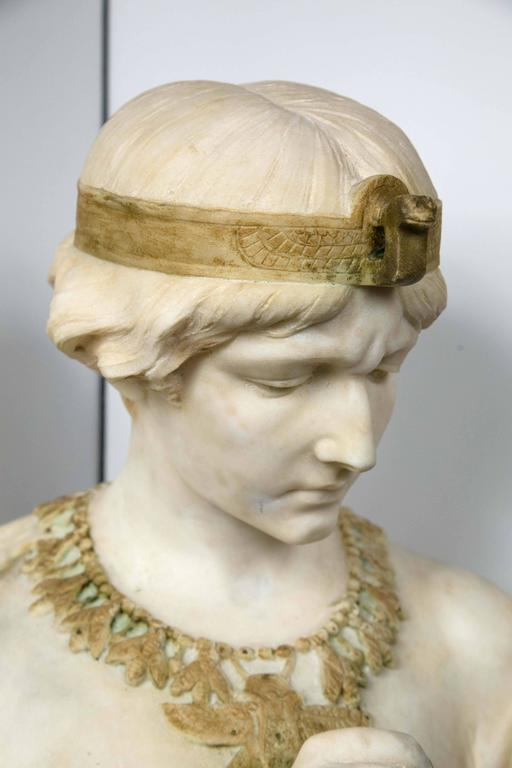 Beautifully carved unusual bust with contrasting marble highlights of an arm band with scarab, head band with snake head, necklace of bees (?) and drop central medallion with wings, and the asp in her right hand. Her hair tied in a bun. Wearing a