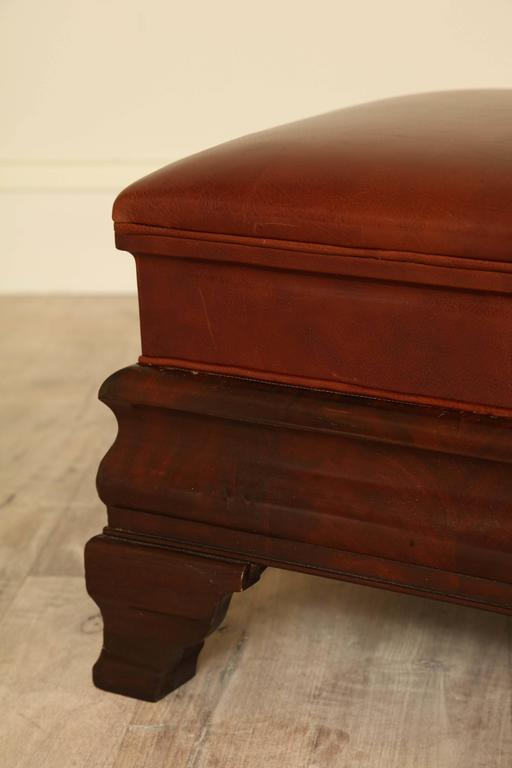 Late 19th century Empire ottoman upholstered in leather with flame mahogany base.