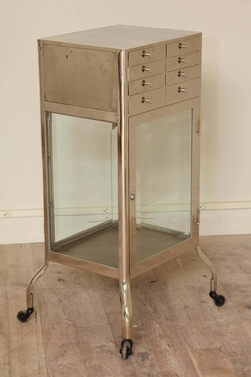 Chrome-plated Industrial cabinet with a bank of eight drawers over a double-sided locking cabinet with beveled glass shelves and doors, circa 1940.