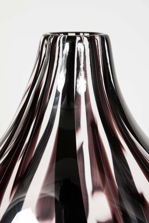 Ikate II is a unique handblown clear and aubergine/dark brown /black, glass sculpture by the Swedish artist Ann Wåhlström. Created to form an elegant teardrop shape, finishing in a refined thin neck, canes of dark coloured glass appear woven into