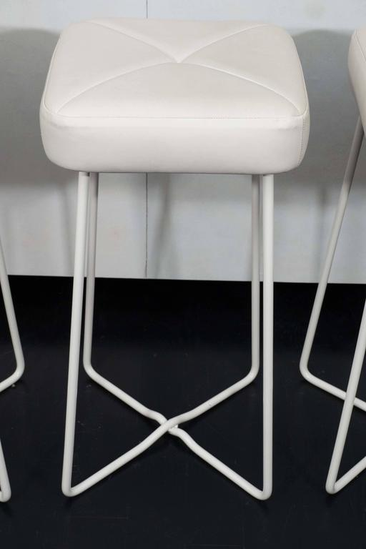 Set of three vintage bar stools from France. Freshly powder coated metal frames with leather upholstery.