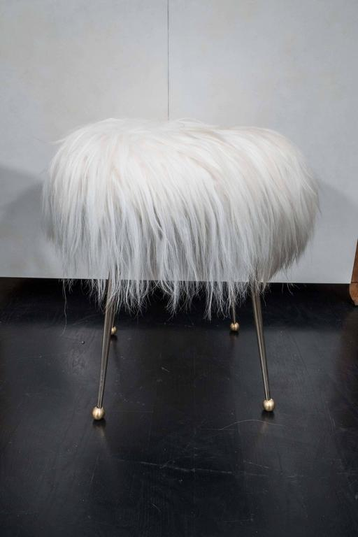 Pair of vintage stools from France. Brass legs with Mongolian fur seats.