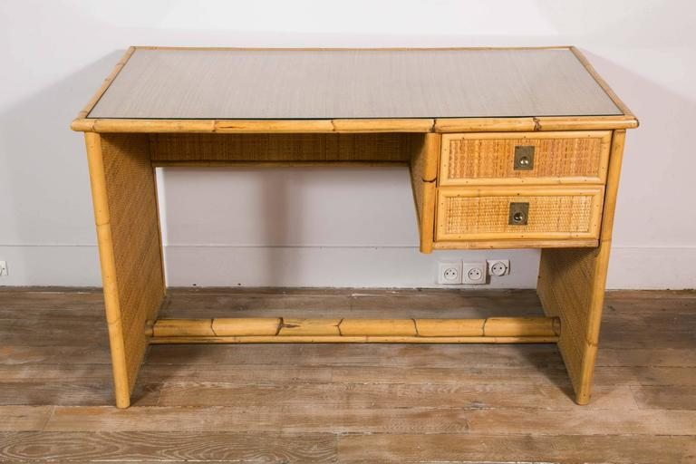 A desk, opening by two drawers on the right hand side. Bamboo structure, woven wicker/rattan panels. Glass top. Design: Dal Vera, Italy, 1960.