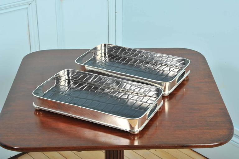 This very attractive pair of nickel-plated serving trays have cut-out handles on both side and are finished with a black faux crocodile lining on the bottom. Each tray measures 14 ¼ in – 36.2 cm wide, 8 in – 20.3 cm deep and 2 ¼ in – 5.6 cm high.