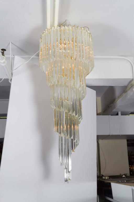 An impressive large scale chandelier, surrounded triedri crystal prisms, spiraling down from a four tier frame in brass. This fixture remains in very good condition, minor wear to metal and minuscule chips to prisms consistent with age and