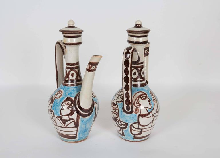 A pair of lidded pottery ewers by ceramic designer Giovanni de Simone, produced in Italy, circa 1960s, each with handle and long spout, decorated with brown, white and blue glazes. Markings include [DeSimone/ ITALY/ 37] to the underside of the