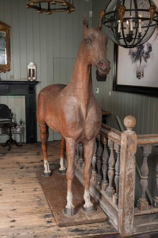 A late 18th-early 19th century full size wooden sculpture of a horse, with tail made from horse hair, resting on a rectangular wooden base mounted on four castors.