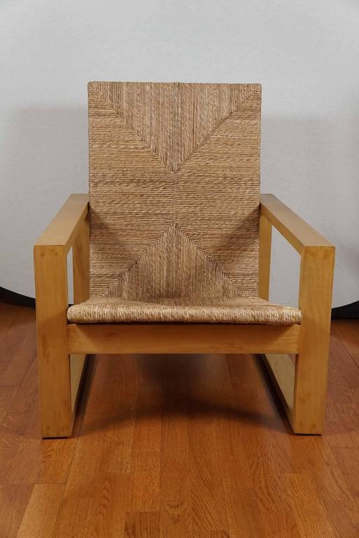Modern square armchair, shown in blonde primavera wood with a natural rush seat and back. Also available in ebonized Rosa Marada wood, with an ebonized rattan seat.