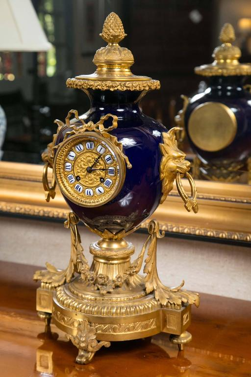Elegant French ormolu mantel clock with stunning cobalt blue vase with lion head handles with crossed sash rings. Clock features intricate gilt face with individual enamel numbers and bow appliqué. Base is comprised of a fluted column with delicate