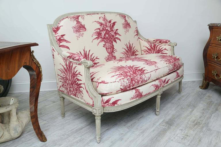 Stunning Louis XVI style loveseat newly upholstered in beautiful cream and cherry topiary fabric.