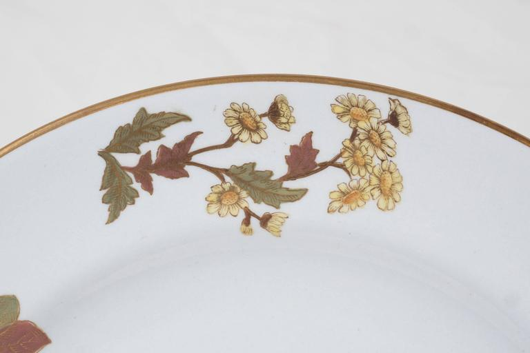 Ten Worcester dishes decorated with flowers in soft purples, green, and rust give this set of dishes a feeling of autumn. The gold veining and outline on the petals creates a lovely a shimmering effect. Made by Royal Worcester in 1877 the dishes