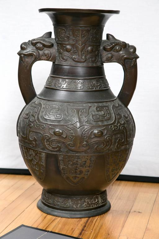 Chinese bronze vase with decoration in the Archaistic style and dragon mythical beast loop handles.