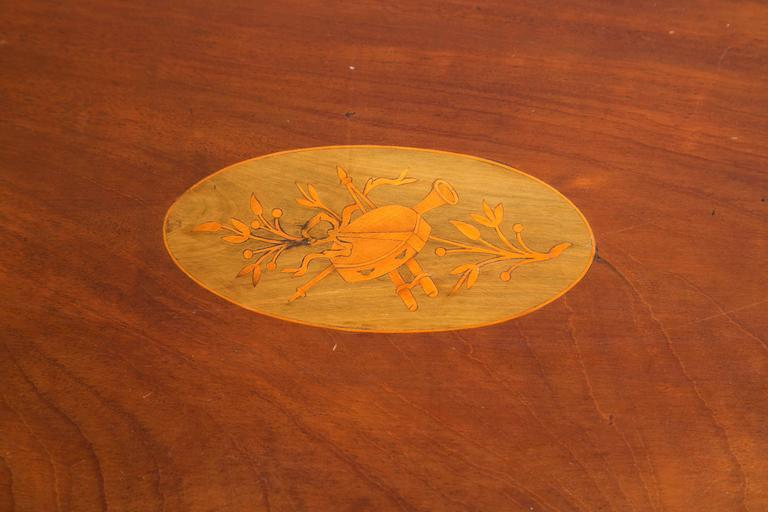An ovoid form tray with two curved handles and a scalloped gallery rim on a felt lined oval Stand to create a low table. The center with musical trophies marquetry.