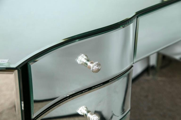 An Art Deco inspired mirrored vanity ladies desk. The beveled all around mirror having a form of clean and sleek lines. The sides with serpentine shape to give this piece a screaming
