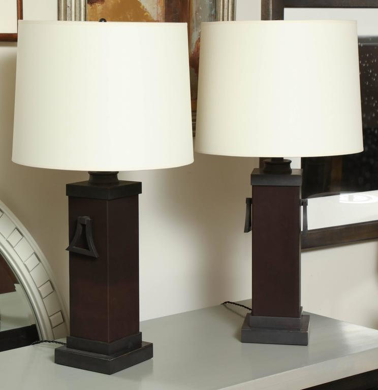 Pair of James Mont square column table lamps; metal components have been finished in bronze, new two-bulb sockets, and the columns have been clad in leather; new silk shades with rolled edges.
