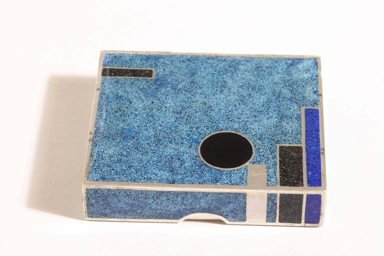 """3 ½"""" wide; 3"""" long; ¾"""" high. 11.20 ozs. gross.  With blue geometric design in champlevé enamel. Design reproduced in the repertoire book of the artist on page 135.  Inscribed Jean Goulden/ 1929/ LXXV/ Goulden silver poincon/ RALLYE-DRACY/ 9"""