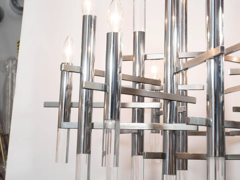 This Mid-Century Modern chrome and Lucite segment chandelier was realized in Italy by the celebrated lighting atelier Gaetano Sciolari. An abundance of polished chrome cylinders, with lucite bottoms, attach to a central chrome rod. The arms are