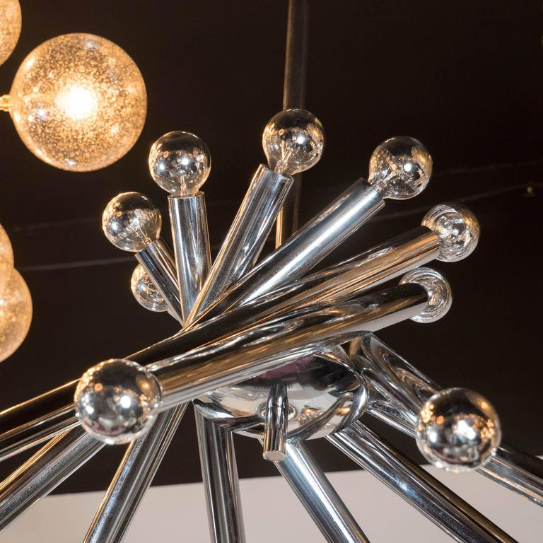 A Mid-Century tubular chrome chandelier in the manner of Gaetano Sciolari. A central chromed dome supports a pinwheel of chrome tubes, each supporting two chrome-dipped bulbs, totaling 18 in all. A chrome rod supports the piece. It has been