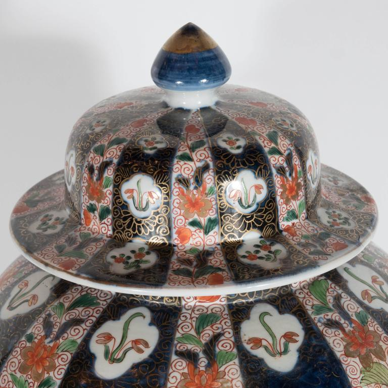 This gorgeous pair of large-scale lidded vases/ urns are decorated with a hand-painted beautiful floral /fauna and geometric decoration. The color palette is all rich jewel tones with a pearl background. These were purchased at William Doyle