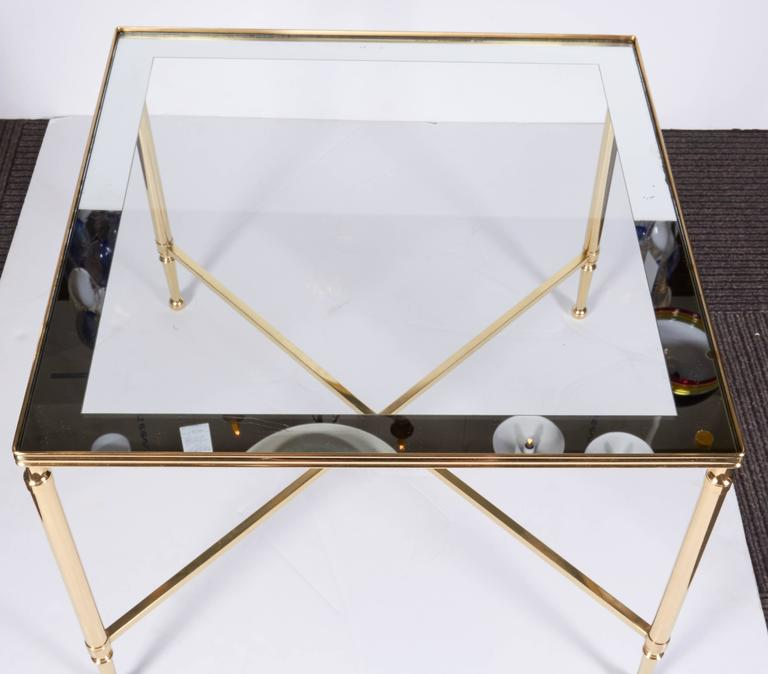 A lovely side or coffee table by French crystal company Christofle. Solid brass construction in a Neoclassical design. Glass top with mirror boarder. Original