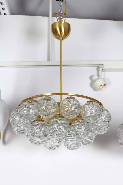 Striking Mid-Century pendant chandelier with two rows of suspended ice glass spheres and one in center, all on a satin brass frame. Uses six chandelier type bulbs, 40W max each. Rewired for use in the USA.