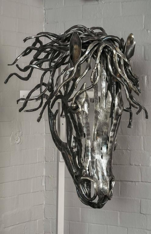 A fine and striking model of a horse's head, hand-forged and uniquely fashioned in textured bar steel by Charles Elliott for John Bly. Equally suitable for internal or external decoration. Charles was inspired by his wife's love and understanding of
