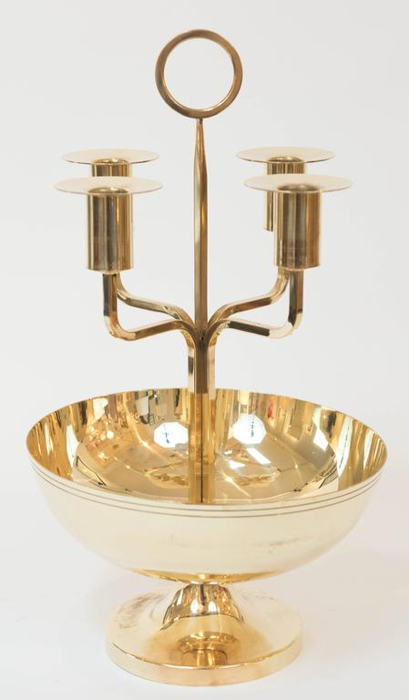 This candelabrum by American designer Tommi Parzinger has been professionally polished to its natural sheen. It has removable bobeche and is stamped: Made by Dorlyn Silversmiths.