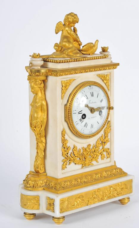 A fine quality French 19th century gilded ormolu and white marble mantel clock, signed Festeau of Paris. Having a cherub with a bow and arrow on top, the enameled clock face with eight day chiming movement. A pair of caryatids mounted on either side