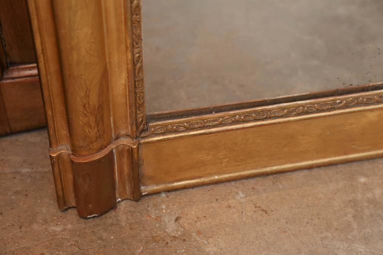 19th century Louis Philippe water gilt mirror with interior raised detail and exterior etched perimeter band ending in two plinths at base. Wear and cracks to the gilt surround.  Original mercury mirror glass.