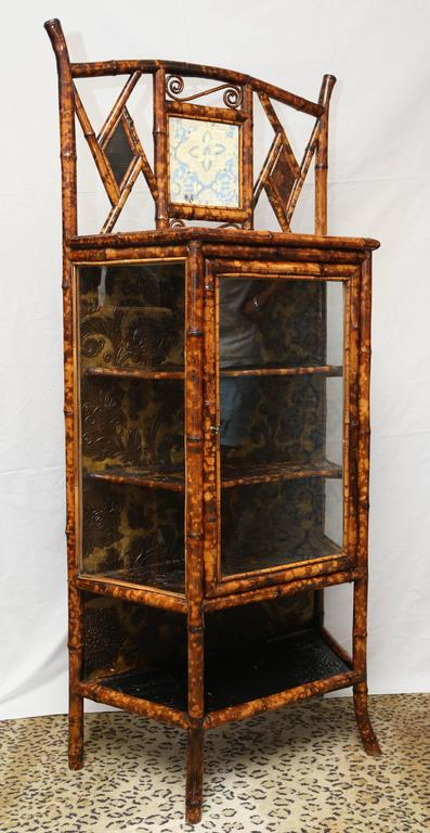 A nice English lacquer bamboo cabinet or bookcase, the pierced back inset with a beveled square mirror flanked by lacquered panels, the lacquered trapezoidal top with a glazed door opening to a shelved interior, over a medial shelf on Sabre legs.