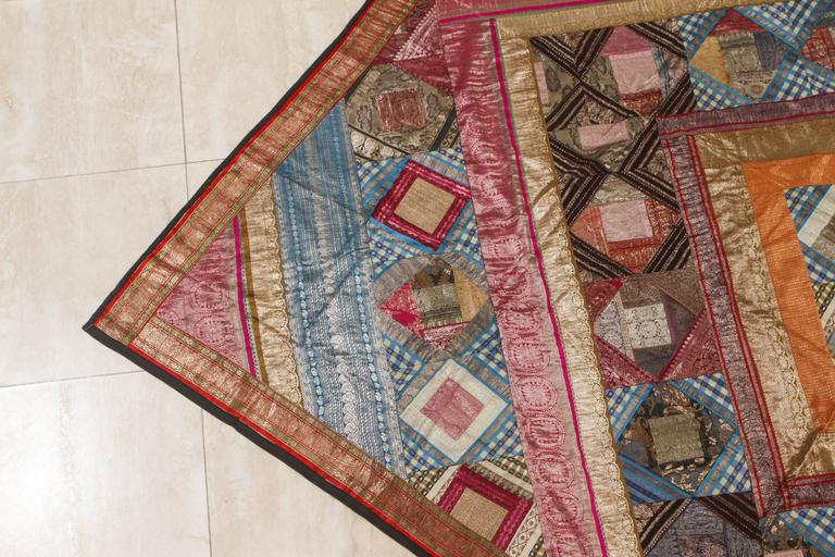 Indian silk sari tapestry quilt patchwork bedcover. A king-size bedspread handcrafted from vintage polychrome silk sari borders. Silk quilted with chevron diamond pattern. Indian patchwork of silk saris borders hanging tapestry or bed cover.