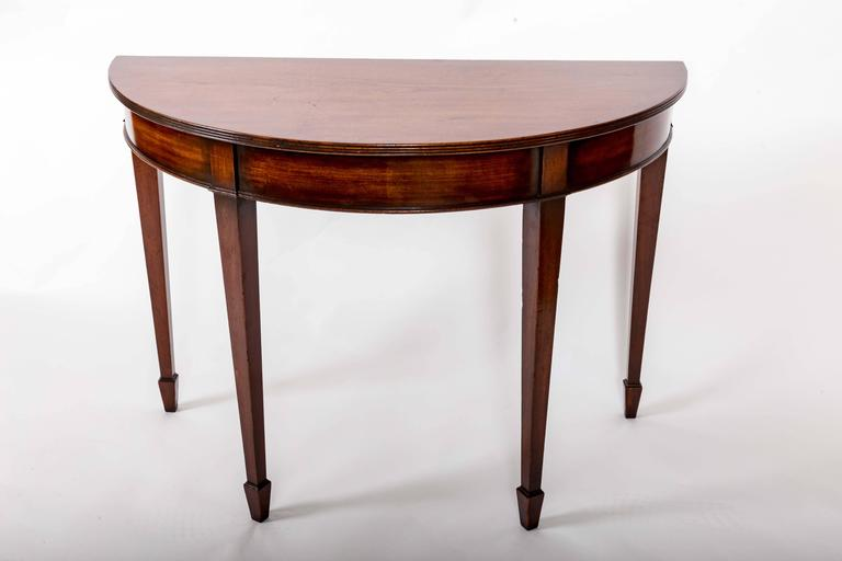 Demilune consoles with reeded edge on top, spade feet and molded apron skirt.