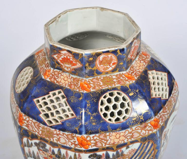 A very impressive 19th century Japanese Imari vase having unusual pierced panels, a classical scene of a vase of flowers, also one of people under pagoda looking out at horse galloping into the distance. We are able to lamp this vase if needs be