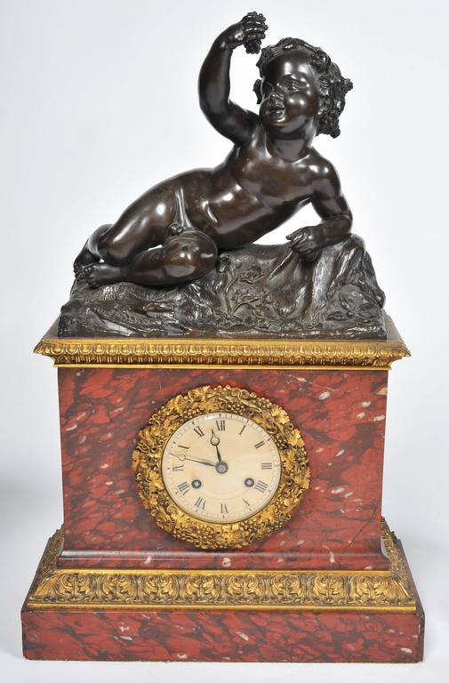 A very pleasing French 19th century rouge marble and gilded ormolu clock garniture. Having a bronze reclining putti holding a bunch of grapes. The silvered dial has an eight day bell chiming movement, the matching pair of bronze tazzas mounted on