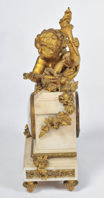 A very pleasing 19th century French gilded ormolu and white marble mantel clock, having a cherub holding a torch and a bow and arrow, leaning against the inset eight day chiming clock.