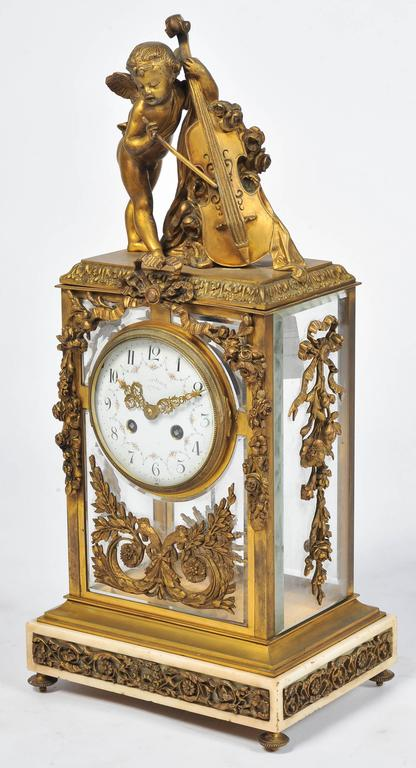 A very good quality 19th Century French gilded ormolu mantel clock. Having a cherub playing a base violin, a four glass case mounted with ormolu foliate and swag decoration, an eight day hour and half hour chiming movement, set on a white marble