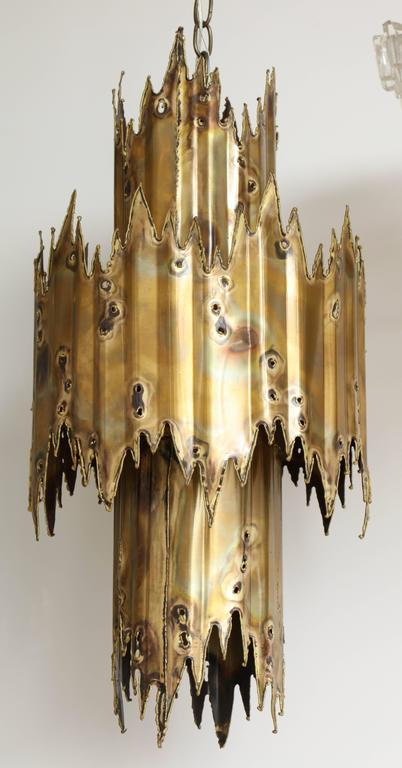 Mid-Century brutal style chandelier made from two layers of aged torch cut brass. Chandelier creates an amazing ambient glow when on. Suspended on an aged brass chain with canopy. Rewired for use in USA using three chandelier sockets and one center