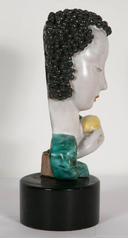 Eve with an apple made in ceramic by the famous Austrian Goldscheider workshop. On a wooden base. Signed inside, circa 1933. The little bust is characteristic of the works its designer - Rudolf Knörlein (1902-1988) - realised over the span of nearly