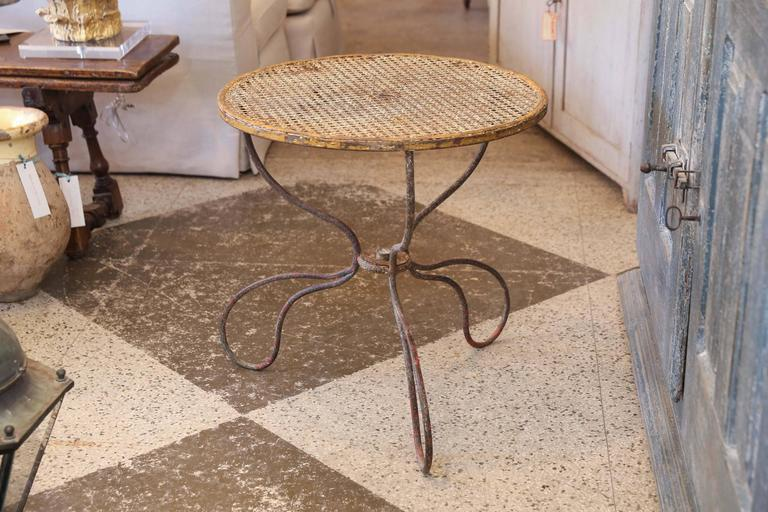 French garden table with metal caned woven top. Unusual, elegant shaped iron base, Wonderful original patina.