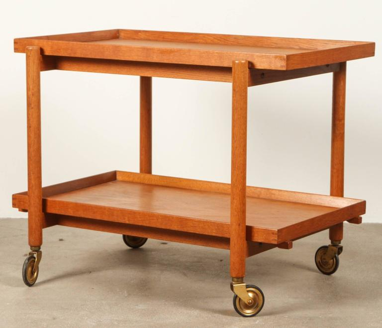 Mid-Century teak Danish bar cart with removable bottom tray and sliding top tray with brass feet details.