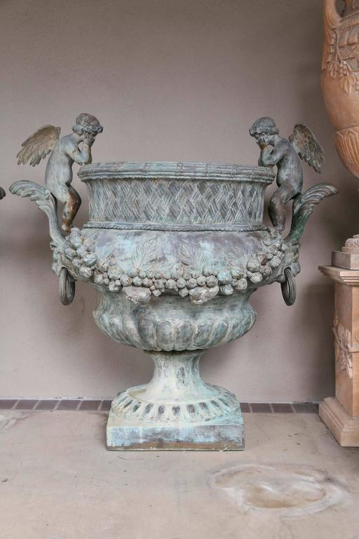 Grand scale planters made of bronze in a verde patina. Winged angels  Sit along each side facing inward. A foliate garland drapes the main body of the planters. Vintage with just the right amount of aging.