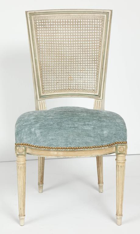 A set of refined and striking Louis XVI style dining chairs. These beautiful chairs are painted is a soft, creamy white with blue/gray accents. The squared back is caned and the slightly rounded seat is upholstered in a pale blue chenille with
