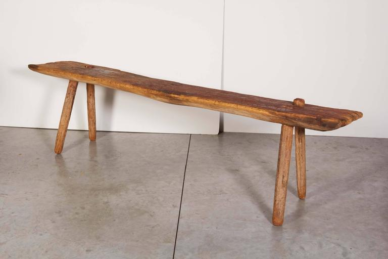 An incredible and unusual Primitive bench with a thick seat, simple legs and a wonderful faded red color that can only be created by years outdoors in the sun. The long seat is very thick, shows the hand of the maker and the impact of time on this