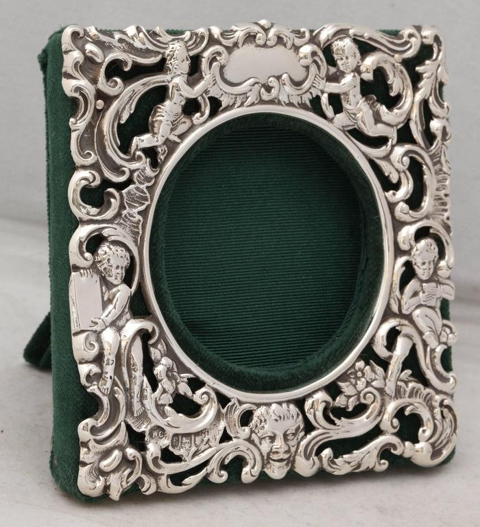 Victorian, sterling silver picture frame, London, 1901, William Comyns maker. Decorated with cherubs and swirls and having a face at the bottom. Vacant cartouche. Backed in dark green velvet. 4